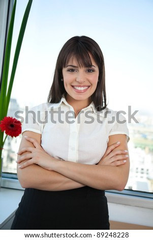 Portrait of happy businesswoman with her arms crossed and smiling - stock photo