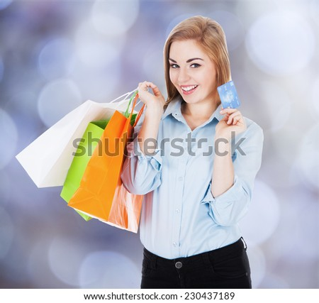 Portrait of happy businesswoman with shopping bags and credit card against colored background - stock photo
