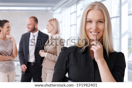 Portrait of happy businesswoman with team at office.