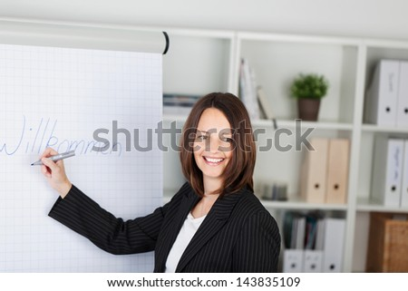 Portrait of happy businesswoman writing welcome sign on paper at office - stock photo