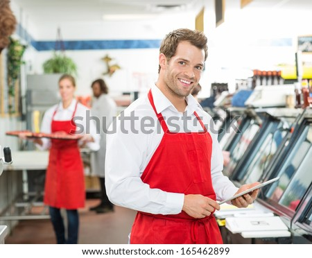 Portrait of happy butcher holding digital tablet at store with colleagues working in background - stock photo