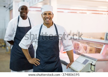 portrait of happy butchery workers standing next to scale - stock photo