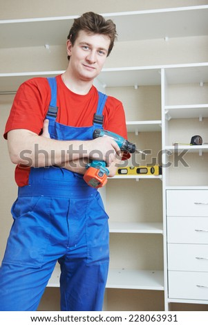 Portrait of happy carpenter worker in front of home built-in cupboard - stock photo