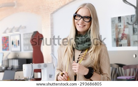Portrait of happy casual trendy caucasian blonde fashion designer businesswoman at studio. Smiling, standing, looking at camera. - stock photo