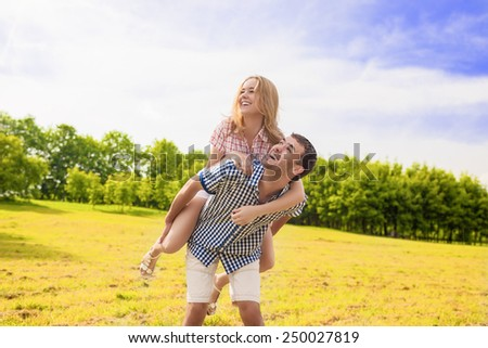 Portrait of Happy Caucasian Couple Playing Outdoors in Summer. Having Fun While Piggybacking and Happiness Lifestyle Concept. Green Forest Environment. Horizontal Image Composition - stock photo