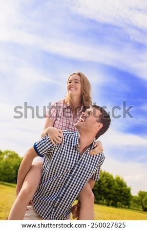Portrait of Happy Caucasian Couple Playing Outdoors in Summer. Having Fun While Piggybacking and Happiness Lifestyle Concept. Green Forest Environment. Vertical Image Composition - stock photo