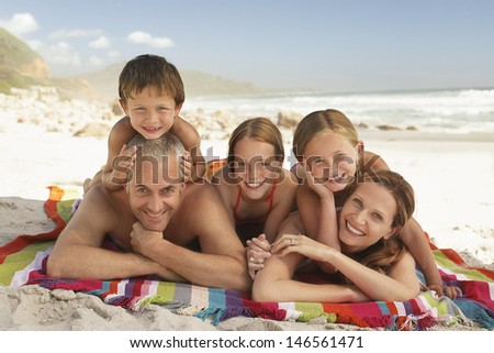 Portrait of happy Caucasian family lying together on blanket at beach - stock photo