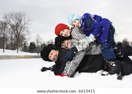 Portrait of happy Caucasian family of four lying stacked on top of each other in snow smiling at viewer. - stock photo