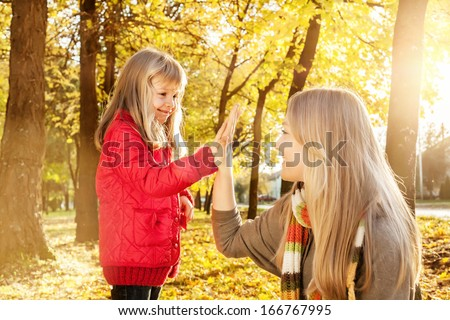 Portrait of happy,caucasian sisters smiling and giving high five in the park  - stock photo