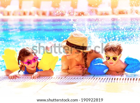 Portrait of happy cheerful family having fun in aquapark, swimming in the pool, relaxing in luxury summer resort, holidays and vacation concept - stock photo