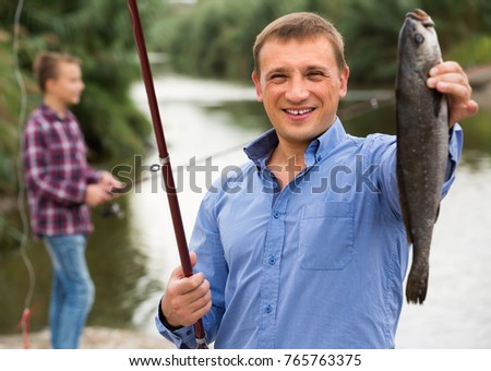 portrait of happy cheerful  man showing fresh catch fish on lake shore