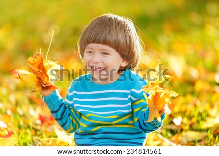 Portrait of happy cheerful smiling boy with yellow leaves. Autumn fall in the park - stock photo