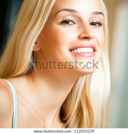 Portrait of happy cheerful smiling young beautiful blond woman, indoors - stock photo
