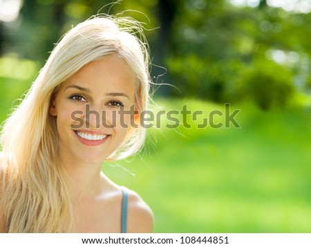 Portrait of happy cheerful smiling young beautiful blond woman outdoors, with copyspace - stock photo