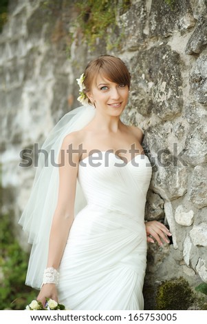 Portrait of happy cheerful smiling young beautiful bride outdoors, against break wall