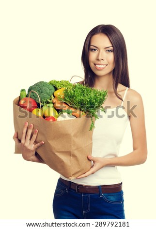 Portrait of happy cheerful woman holding grocery shopping bag with healthy vegetarian raw food, in tank top casual clothing. Healthy eating and dieting concept. - stock photo