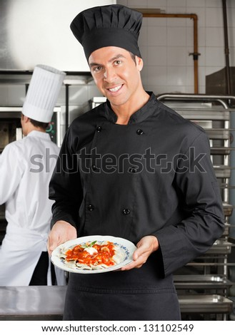 Portrait of happy chef presenting dish with colleague in background at restaurant kitchen