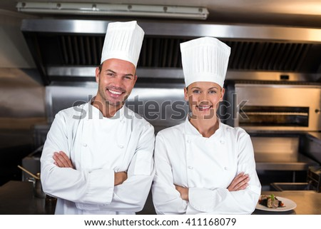 Portrait of happy chefs standing in commercial kitchen - stock photo
