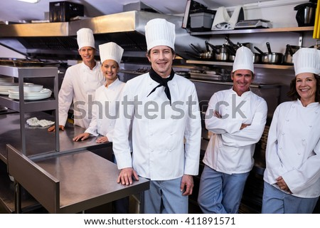 Portrait of happy chefs team standing together in commercial kitchen - stock photo