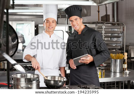 Portrait of happy chefs with digital tablet cooking food in commercial kitchen