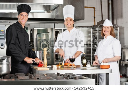 Portrait of happy chefs working in industrial kitchen