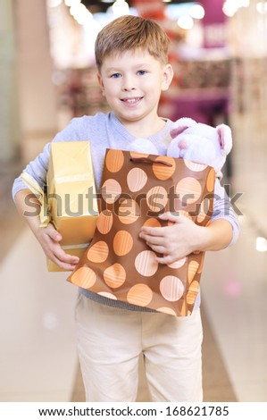 Portrait of happy child holding paperbag with teddy bear and giftbox - stock photo