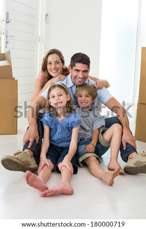 Portrait of happy children and parents sitting on floor in their new house - stock photo