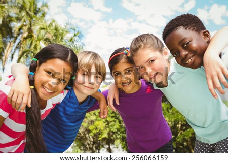 Portrait of happy children forming huddle at the park - stock photo