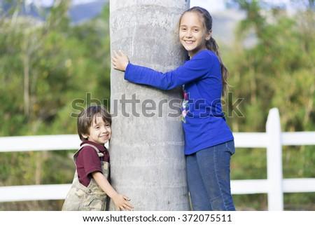 Portrait of Happy Children Hugging a Tree - stock photo