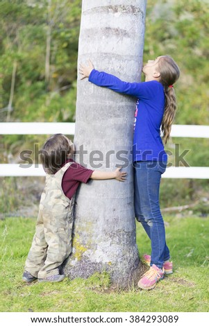 Portrait of Happy Children Hugging a Tree - stock photo