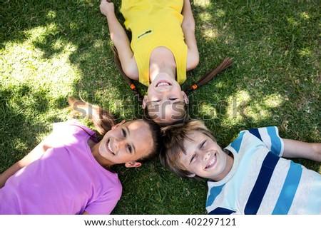 Portrait of happy children lying on grass in park - stock photo