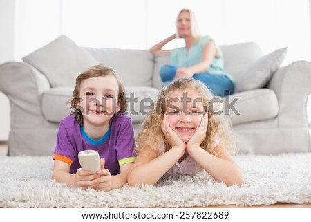 Portrait of happy children lying on rug while woman sitting on sofa at home - stock photo