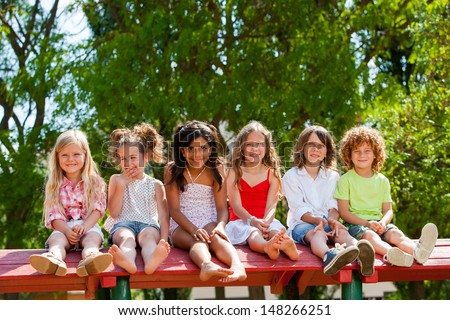 Portrait of happy children sitting together wooden structure in park. - stock photo