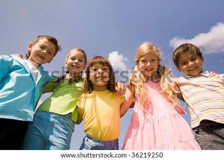 Portrait of happy children smiling while embracing each other on background of blue sky