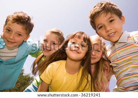 Portrait of happy children smiling while embracing each other with pretty girl in front - stock photo