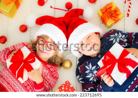 Portrait of happy children with Christmas gift boxes and decorations. Two kids having fun at home - stock photo