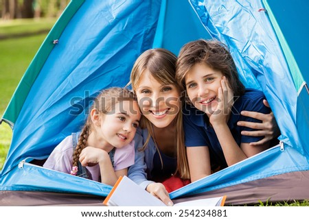 Portrait of happy children with mother holding book in tent at park - stock photo