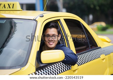 Portrait of happy chinese taxi driver in yellow car smiling and looking at camera - stock photo