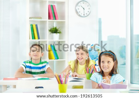 Portrait of happy classmates at workplace during lesson - stock photo