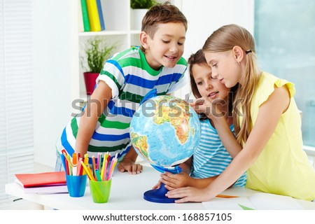 Portrait of happy classmates at workplace studying globe in classroom - stock photo
