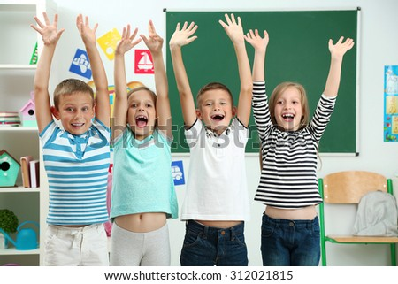 Portrait of happy classmates looking at camera in classroom - stock photo