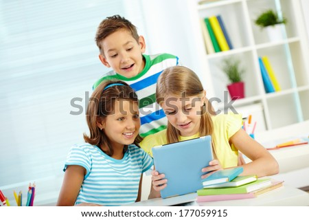 Portrait of happy classmates looking at digital tablet astonishingly