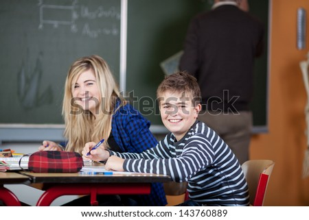 Portrait of happy classmates sitting at desk with teacher writing on blackboard in classroom