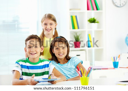 Portrait of happy classmates with digital tablet in classroom - stock photo