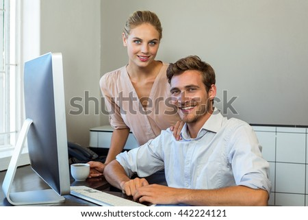 Portrait of happy colleagues at desk in office - stock photo
