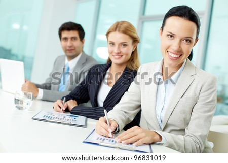 Portrait of happy colleagues looking at camera with focus on pretty woman in front - stock photo