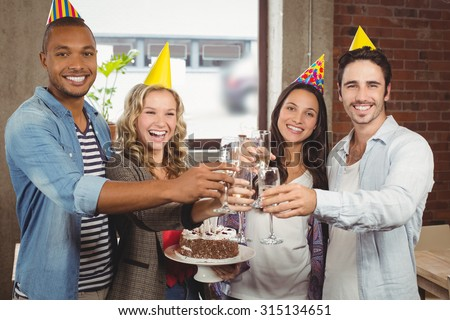 Portrait of happy colleagues toasting with champagne in bright creative office - stock photo