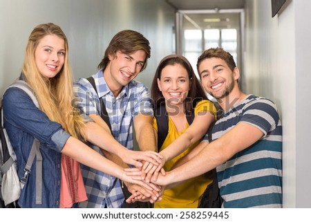 Portrait of happy college students placing hands together - stock photo