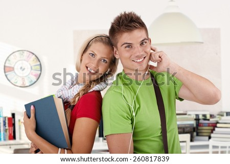 Portrait of happy college students sharing earbuds as listening to music. - stock photo
