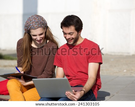 Portrait of happy college students sitting outdoors and working on laptop - stock photo